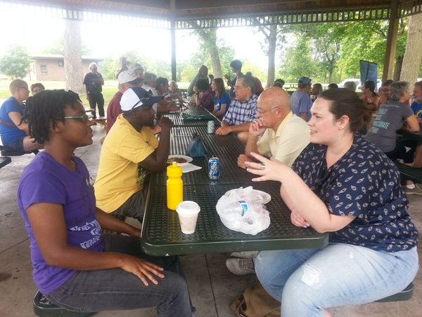 Photo of conversation at one of the picnic tables.
