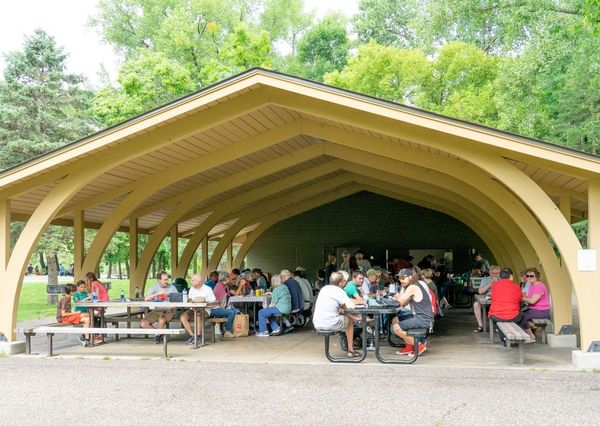 Distance photo of picnic pavilion full of attendees.
