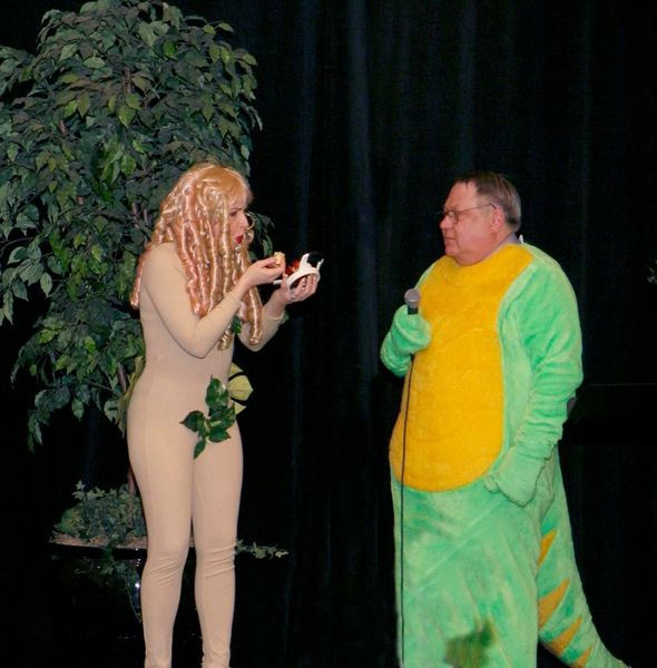 Photo of Eve and a dinosaur on stage at Solstice dinner.