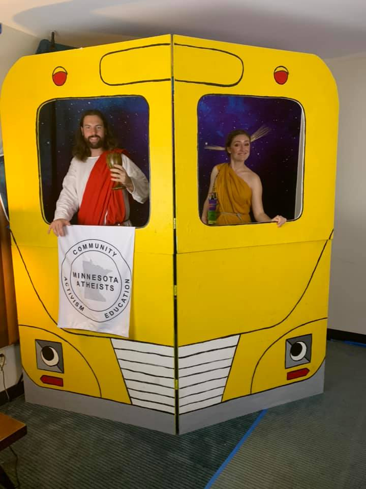 Photo of attendees cosplaying gods in school bus prop.