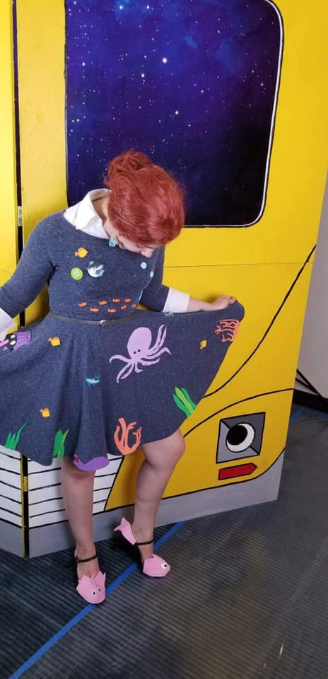 Photo of person showing off a dress covered in sea animals.