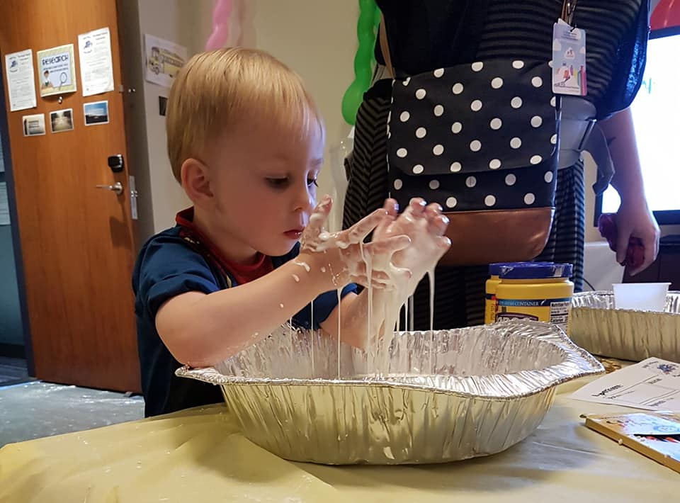 Photo of small child watching corn starch goop drip through fingers.