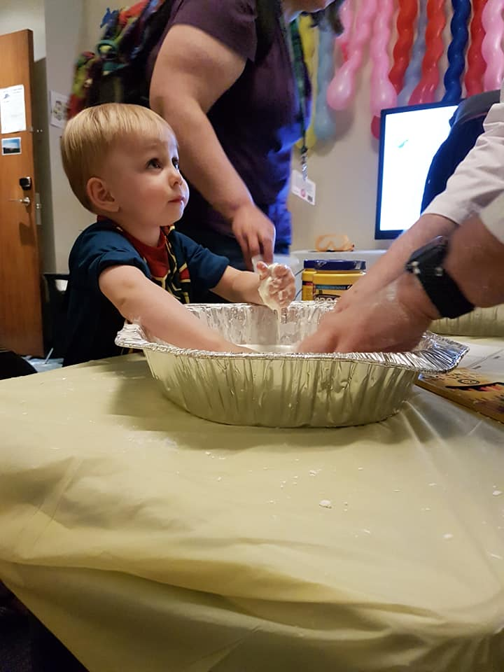 Photo of small child and adult with their hands on corn starch goop.