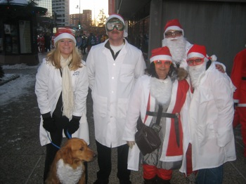 Photo of several people in white tops and Santa hats.
