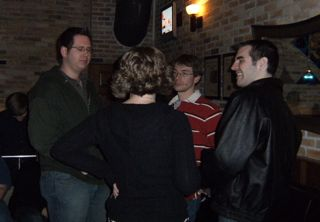 Photo of small group standing in a bar.