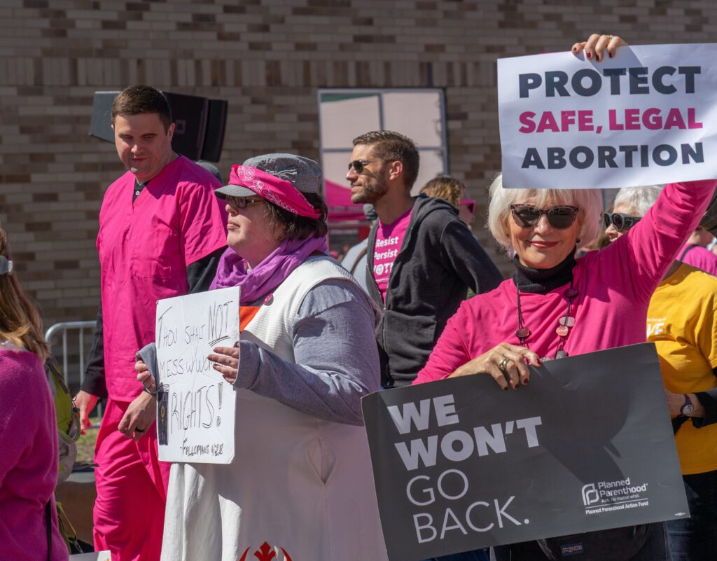 """Photo of pro-choice protesters, one holding a sign that says """"Protect Safe, Legal Abortion""""."""